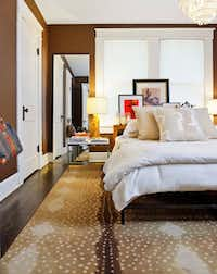 """""""It's totally a fashion rip-off, but local,"""" Flannery says of the custom bed he had a Dallas metalworker duplicate from a Calvin Klein ad. Linens and pillows are Sferra. The Karastan """"Aberdale Antelope"""" rug has """"the same great, chic, go-with-everything quality that leopard and zebra do."""" Hanging from the door knob: Flannery's monogrammed Goyard tote."""