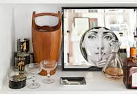 Flannery's living-room built-in bar, kitted out with Fornasetti plate and 1970s erotica tumblers.