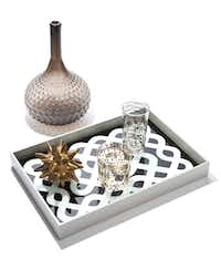 "DwellStudio by Global Views glass vase, $63, lacquered wood ""Labyrinth"" tray, $148, ceramic urchin, $17, and glasses decaled in silver and 24-karat gold, $63 and $73, all from a collection at Stanley Korshak Home and Rutherford's"