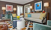 """""""This would be a heart-attack level of change for some clients, but Allane's artistic, she was into it,"""" says designer Charles Taylor of the fearless redo he and design partner Breck Woolsey pulled off for client Allane O'Neil. Vibrant paintings by Poteet Victory pop against the formal living room's chocolate walls. The pieced-cowhide rug is a David Hicks-inspired motif from the DeManos collection at Interior Resources. A pair of aqua cotton-velvet club chairs are from Mecox Gardens; the sofa is a reupholstered Debris Antiques find. The designers custom-crafted the white-lacquered coffee tables from bendy board. The mirrored console is a former display piece from Grange Hall, now topped by a pair of mid-century lamps scored at a garage sale."""