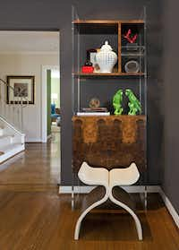 The burled walnut-and-Lucite curio cabinet is a prototype piece from the designers' Breckinridge Taylor line at Mecox Gardens. The leather-and-wood vintage stool was found at Again & Again.