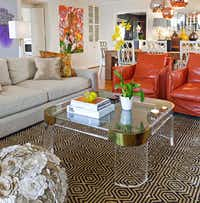 The family room's vintage acrylic coffee table was cut down from a taller piece handcrafted by Charles Hollis Jones, acclaimed for pioneering the use of acrylic in furniture design. Bonus: It doesn't block the view of the striking geometric rug from Interior Resources. Orange leather slipcovers (yes, slipcovers) on the Mecox Gardens chairs makes it easy to change up the room's look.