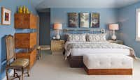 """""""We wanted something really serene and spa-like for the master bedroom,"""" says Taylor, who painted the walls soothing sky blue. The vintage Mastercraft brass headboard is from Antiques Moderne, with custom bedding in an ikat fabric from Schumacher Dallas. The white leather bench is custom, and the designers created the tall credenza by stacking three burled wood cabinets with Lucite box dividers. Woolsey livened up the French side chairs with vinyl snakeskin seats."""