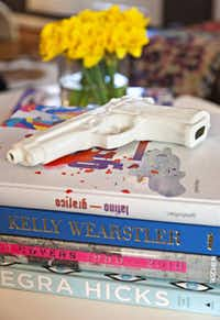 A Seletti porcelain handgun from Nest adds a wink of danger to a stack of design books.