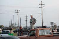 Military personnel and civilians wait in a parking lot outside of the Fort Hood military base for updates about the shooting that occurred inside on Wednesday, April 2, 2014, in Fort Hood, Texas. (AP Photo/Tamir Kalifa)Tamir Kalifa - AP