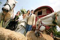 "Portrait perfect: The fictional bride and groom pose in front of the authentic 1800s Gypsy wagon. They are flanked by two of Dowd's white quarter horses, a mother and daughter named Blanca and Ashes. Both mares wear a chain of roses around their necks from Cebolla Fine Flowers. The bride wears a pistachio-colored Monique Lhuillier Venice gown from Warren Barrón Bridal (53 Highland Park Village, 214-526-8400, warrenbarron.com). The silk-gazar skirt is hand-tufted; the bodice is hand-embroidered and beaded on lace. The groom wears a vintage-inspired look: a wheat-colored linen blazer, French-blue linen pants and a knit tie, reminiscent of those worn in the 1920s. One member of the bridal party wears an authentic Alsatian outfit. ""My mother wore this costume on almost every major holiday,"" says Dowd. Incorporating an heirloom garment among the wedding party's contemporary attire is a beautiful way to meld tradition with a modern ceremony."