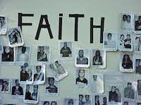 """A board with """"Faith"""" spelled out in black electrical tape near New York's Union Square on Sept. 15, 2001 is filled with photos and details of World Trade Center employees missing after the Sept. 11 attacks."""