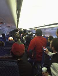 A cellphone photo provided by Jessica Mill shows passengers looking toward a disturbance at the front of an American Airlines jet at Dallas/Fort Worth International Airport.