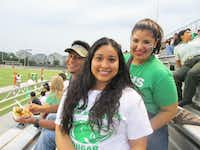 Bryan Adams counselor Joel Ledezma (left), Esmeralda Cortez and student Janelle Torres cheer on the Bryan Adams Cougars at a football game last year.