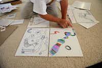 Franklin Wright, 8, explains the rules of one of the board games he created at his Frisco home earlier this month.ROSE BACA