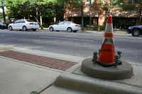 A traffic cone sits over the base where the pole for the future High-intensity Activated Crosswalk will be installed on McKinney Avenue between Allen and Worthington streets.