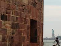 Castle Williams overlooks the busy New York harbor and the Statue of Liberty.