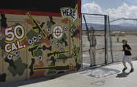 A child runs by the Arizona gun range where instructor Charles Vacca was accidentally killed Monday while showing a 9-year-old girl how to shoot an Uzi.John Locher - The Associated Press