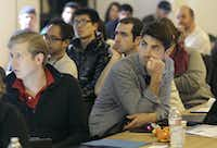 In this Saturday, Feb. 8, 2014 photo, Segah Meer, right, and other participants listen to speakers during the FinCapDev San Francisco Hackathon in San Francisco. A record 1,500 hackathons around the world are planned for this year, up from just a few dozen in 2010, and their focus is broadening from developing lucrative apps to solving problems with coding for an array of issues including dental, fashion, immigration, transgender and social justice. (AP Photo/Jeff Chiu)Jeff Chiu - AP