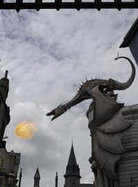 A dragon breathes fire from atop Gringotts Bank at Diagon Alley at the Wizarding World of Harry Potter. The new attraction opened Tuesday at Universal Orlando. Visiting both Hogsmeade and Diagon Alley requires a park-to-park ticket.John Raoux  -  AP