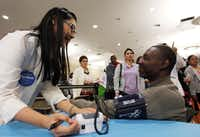 Helen Vo, a health care volunteer from Kroger, measured Stephen Stewart's blood pressure during the Be Covered Texas health fair.