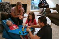 The members of the Howard family, of Carrollton, play together on Labor Day. Harper (left) helped her mother, Penny, sister, Lily, and father, Dustin, pick the colors for the Play-Doh snowman they made by moving her head slightly to answer yes-and-no questions. Harper, 3, has a rare genetic disorder that causes constant seizures and developmental delays, and family and friends will raise funds for research that could help her with the second annual Run4Hope on Sept. 7 in Coppell. For story and more photos, see Page XX.