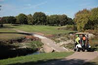 <TypographyTag14>Rick and Lucas Moffitt</TypographyTag14> drive the cart path on the third hole of Duck Creek Golf Club.Staff photo by CHRIS DERRETT