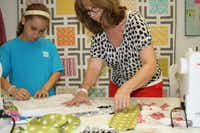 Michelle Kitto helps Elise Little, 9, pin her pattern to the fabric she chose during a summer camp. The girls were making tote bags.