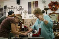 Pat Malone, owner of Ten of Arts, which she co-owns with Lynne Hosid, displays some of her jewlery to patrons, Cindy Randolph and J.T. Randolph. The shop is one of several that sits on the square and has been