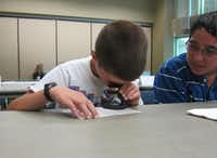 Isaiah Tovar,13,  looks on as Trenton Turek, 10, examines a finger print taken from a window during the first week of Rowlett's youth police academy.