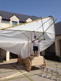 John Leonard works on constructing the family's covered wagon, which is topped with a hang glider made from Chinese bamboo and a paint tarp.