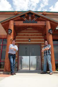 Twin Peaks CEO Randy DeWitt (left) and brewmaster Tom Janik stand in front of the north Irving location's Ice House, a display of the restaurant's draft kegs where the national chain's first brewery will be built. Read the story on Page XX.