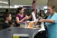 Library clerk Rebecca Hood (left) sacks Meg Guerra and her children's books. Hood has worked at the library for seven years, and said she has seen continued growth and a demand in services.