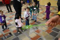 <TypographyTag11>Toddlers chase bubbles </TypographyTag11>during Juega Conmigo. Now in its third year, the program gives the adults in northwest Dallas a forum for about an hour each Thursday to discuss parenting challenges they faced that week and offers them a chance to improve interactions they have with their children. <252> <252>ROSE BACA