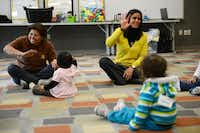 Adriana Villa Baird (right), program manager, leads a song during Juega Conmigo, a free program of weekly parent-child playtimes at the Bachman Lake Branch Library in Dallas. The program, administered by the Center for Children and Families at the University of Texas at Dallas, is designed to foster strong parent-child relationships and children's growth through play sessions.Photos by ROSE BACA