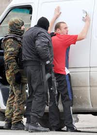 Armed masked men and local militiamen searched a van driver at a checkpoint on a highway connecting the Crimean peninsula to mainland Ukraine on Friday.Viktor Drachev  - Presse
