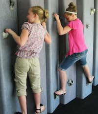Two girls at the Children's Discovery Museum of the Desert, Rancho Mirage, Calif., test strength and agility as they work their way across the rock climbing wall.