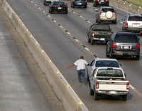 A pickup's driver talks on a cellphone while trying to catch a motorist in a white sedan after a near collision during morning rush hour on westbound LBJ Freeway near Marsh Lane. Traffic is moving slowly and HOV lanes are closed during the first phase of the highway's reconstruction.