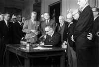 President Lyndon Johnson signed the Civil Rights Act in the White House in 1964. Some doubt Kennedy could have won passage.
