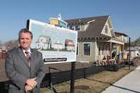 Coppell City Manager Clay Phillips stands next to the first three office cottages in Old Town's Main Street Coppell development.neighborsgo file photo