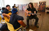 Instructor Kenny Withrow gives a guitar lesson to brothers Jose Christopher Torres (left), 16, and Joel Torres, 10, at the Oak Cliff Cultural Center on Jan. 17, 2014, as part of La Rondalla, a series of free classes developed by nonprofit Big Thought's Thriving Minds.ROSE BACA/neighborsgo staff photographer