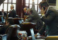 In a frame grab from video, Texas State Rep. Ken Legler District 144 (R-Pasadena), (center, with arm raised) is captured reaching over to the desk of a fellow Republican to cast a vote, in a video sequence showing him casting votes on three different House members' desks, during Texas House proceedings on Wednesday.
