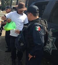 Leonardo Quintero, a member of a local self-defense force, pours lemonade for a federal police officer at a checkpoint near Nueva Italia, in western Mexico.