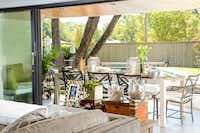 The Preston Hollow house's wall of glass opens to a backyard pool, patio and dining area, frequent site of family get-togethers.