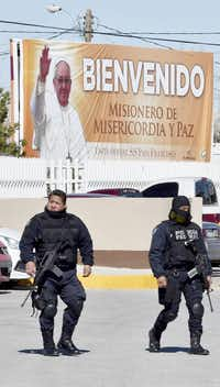 """Federal police patrol near a banner welcoming Pope Francis' """"mission of mercy and peace"""" at the city prison in Ciudad Juárez, one of the sites the pontiff will visit Feb. 17.Yuri Cortez  - Presse"""