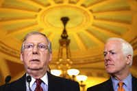 Senate Minority Leader Mitch McConnell, with Texas Sen. John Cornyn, called a group closely allied with Cruz a bully that deserves a punch.