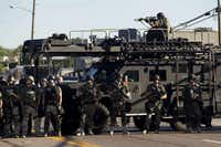 Law enforcement officers, including a sniper perched atop an armored vehicle, watch as demonstrators protest the fatal shooting of Michael Brown, in Ferguson, Mo., Aug. 13, 2014. The police chief of this St. Louis suburb said Wednesday that Brown injured the officer who later fatally shot the unarmed 18 year old — though witnesses dispute that such an altercation occurred. (Whitney Curtis/The New York Times)WHITNEY CURTIS - NYT