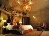 Earth Lodge's Amber Suite features a carved wooden headboard and a deep egg-shaped bath, along with its own steam room, plunge pool, study and kitchen.