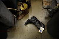 Cowboy boots lay on the floor waiting to be repaired in the back room of Messina Shoe Repair in Farmers Branch. Kenneth Burks and his wife, Nancy Burks, have owned and operated the shop since 1964.Rose Baca  -  neighborsgo staff photographer