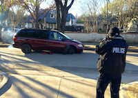 An officer photographs one of two minivans involved in the early morning break-in at the Chanel store. (David Woo)