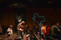Members of The Gathering, a Mesquite-based church, bow their heads during a service at the historic Rodeo City Music Hall in Mesquite. The church recently purchased the historic venue, selling their current property and sending the left over proceeds to their ministry in India.Rose Baca