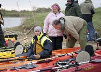 Triple amputee Bryan Anderson gets help preparing to go kayaking from Jim and Sally Dolan.
