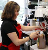 Valarie Floyd prepares a drink in the Skillman store ahead of Monday's opening.