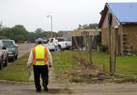 "OSHA's Elias Vela walks the Lancaster neighborhood ravaged April 3 by tornadoes. ""We don't want anybody — whether they are volunteers or not — to get hurt,"" Vela said."