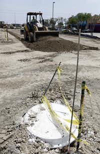 A manhole cover marks where pipes are buried for the collection of rainwater at the Lobb Chrysler-Jeep-Dodge dealership under construction in McKinney. The water will be used to keep the grounds green
